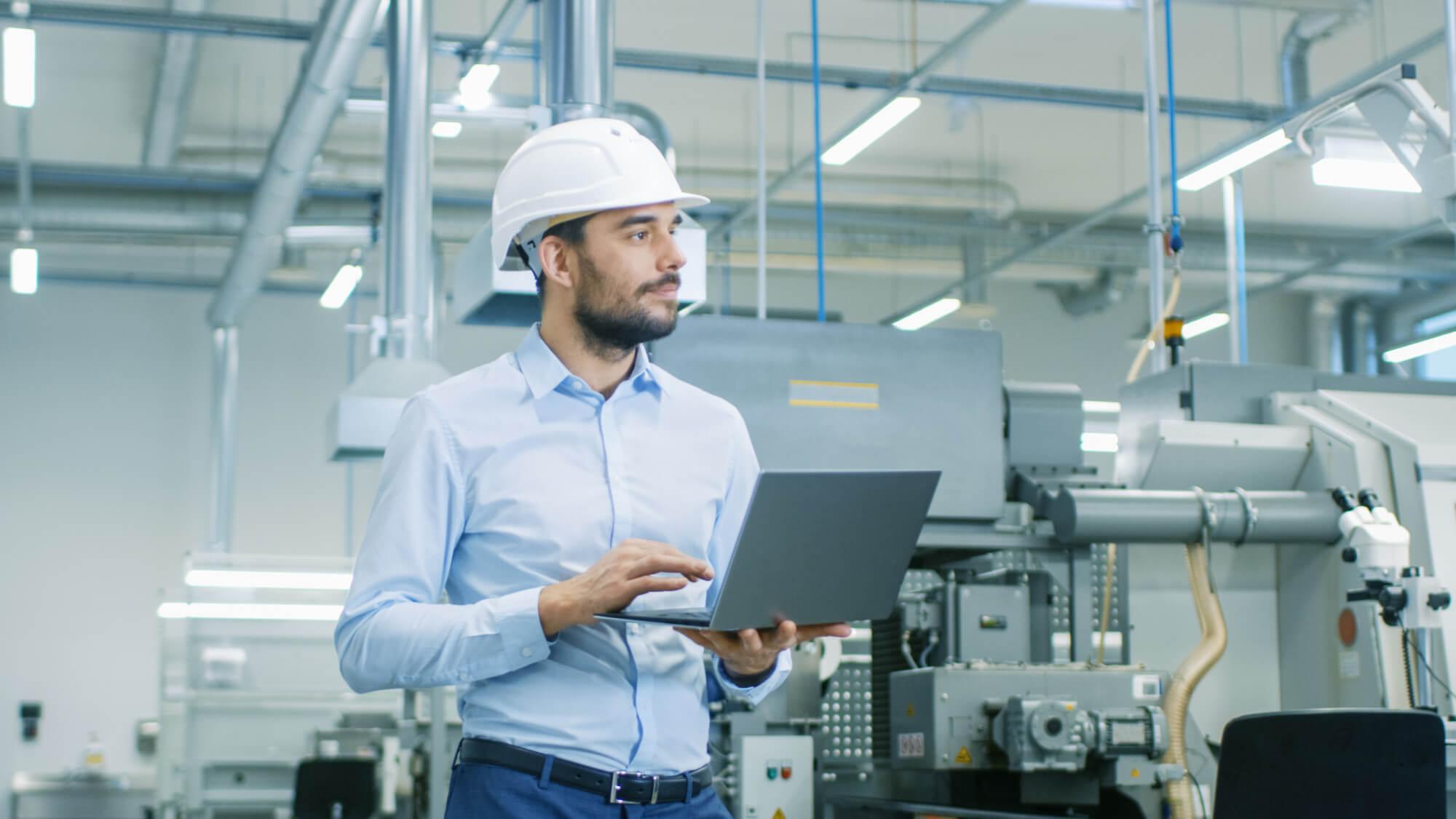 戴着硬帽的总工程师拿着笔记本电脑走过轻型现代工厂。现代工业环境中的成功、英俊男子。